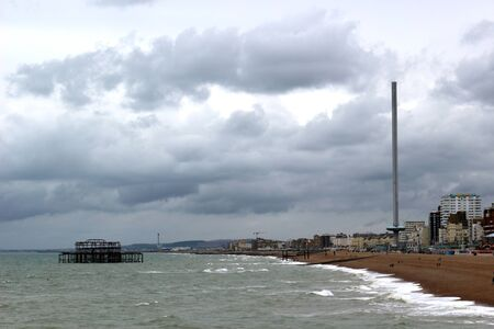 Brighton, East Sussex, England. 9th September 2019. A view from the Palace Pier in Brighton, towards the West Pier and the i360 observation tower on a cloudy day.