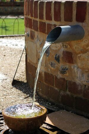 Water pouring from a spout into a bowl outside