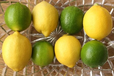 Alternating Lemons and Limes in a glass bowl Фото со стока
