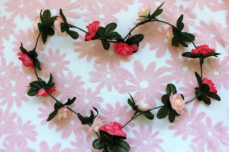 A string of fabric roses in the shape of a heart on a pink flower background