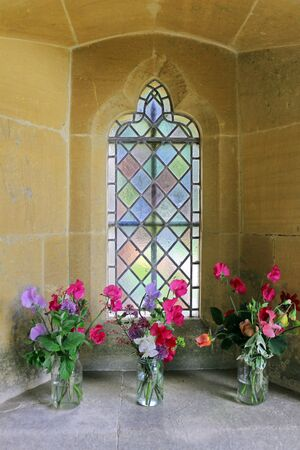 A colorful sweet pea flower arrangement in the alcove of a church window