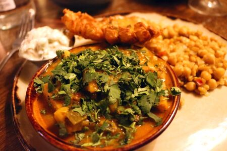 A vegan curry served with various side dishes and garnished with coriander Фото со стока