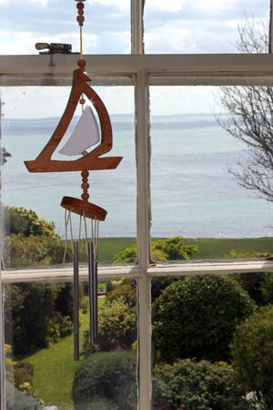 A view of the sea behind a framed window and a wind chime boat