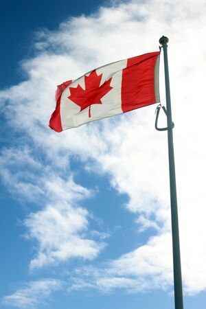 The flag of Canada flying against a blue sky and white clouds Standard-Bild