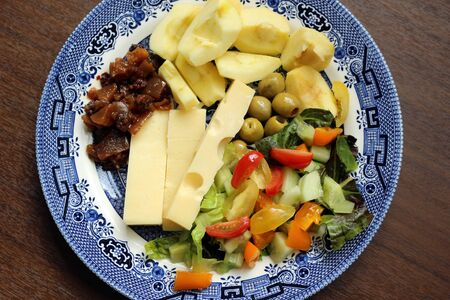 A salad with jarlsberg cheese, apples and sliced vegetables on a plate