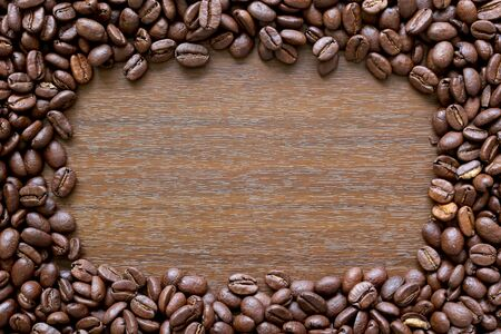 Coffee frame. A border made up of coffee beans around a wood effect background Standard-Bild