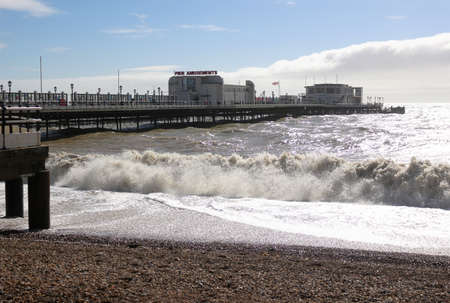 Worthing, West Sussex, England. 11th March 2020. Worthing Pier with waves crashing in the foreground. Editorial