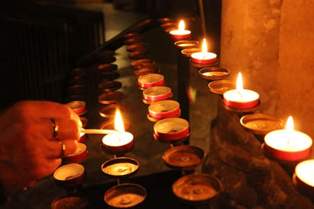 lighting a prayer candle in a church