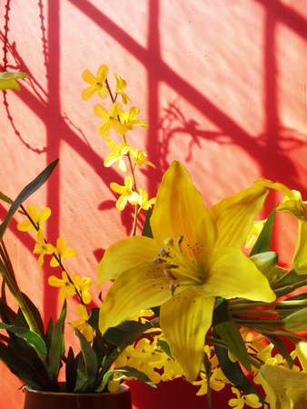 Yellow fabric day lillies by a red wall next to a window