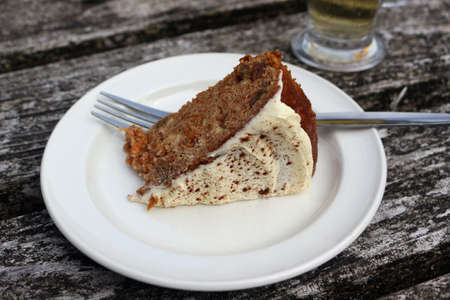 A piece of carrot cake on a white plate