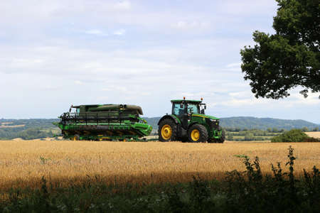 East Meon, Hampshire, England. 6th August 2020. A green tractor and combine harvester in a wheat field Редакционное
