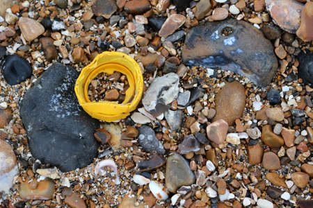 A yellow plastic bottle top on the beach