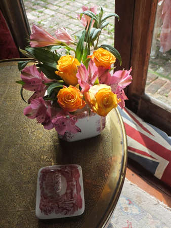 A vase with yellow roses and pink lilies