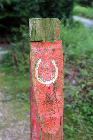 bridle path horseshoe symbol on a wooden post Фото со стока