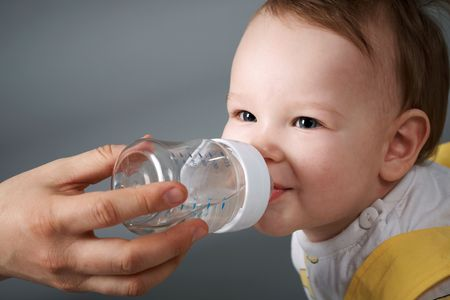 drank: The little boy smiled and drank water from a bottle. Close-up. Stock Photo