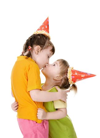 Little girls in festive caps embrace. White background, studio shot.