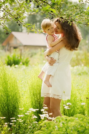 joyfully: Mother holds baby son in her arms. Summer is around the grass and flowers