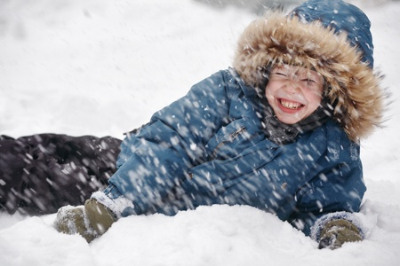 The boy lay on the snow and smiles. Its snowing. Winter. photo