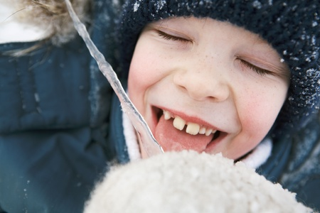 carefree: Boy licking an icicle and laughs. Close-up.