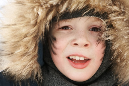 boy in a warm fur hat looks into the camera. Close-up. photo