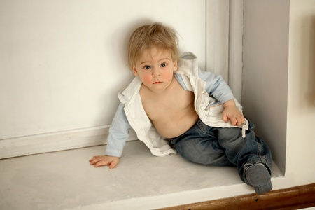 Little boy sits next to a closed door and sadly looks at the camera. photo