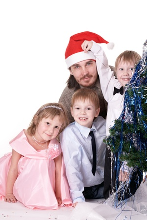 joyfully: A man and three children sitting near a Christmas tree and joyfully look into the camera. Studio, white background Stock Photo