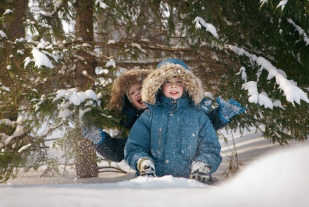 snowbank: Two boys sitting in a snowbank and looked into the camera. Near the trees. Winter Stock Photo