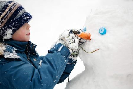 sculpt: The boy sculpts snowman. Winter, outdoors, close-up