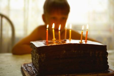 torta con candeline: Un bambino si siede ad un tavolo e guarda una torta con le candeline Archivio Fotografico