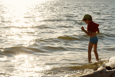 enters: The boy timidly enters the sea and laughing. Summer evening.