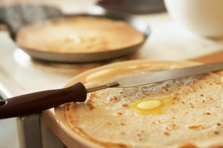 estufa: En la placa es un panqueque dorado con mantequilla. En el fondo es una tortilla caliente en una sartén