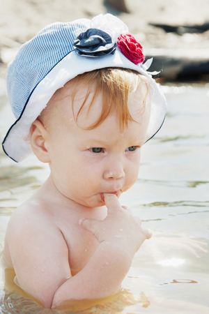 sucks: Little girl sits in water and sucks her finger Stock Photo