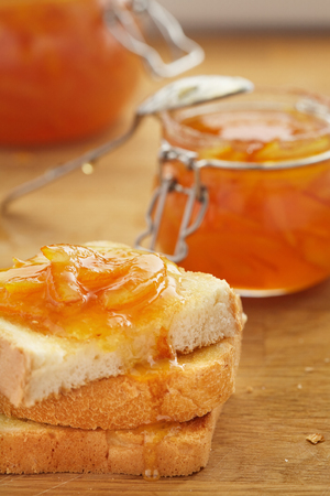 Toasts of white bread are smeared with orange jam. Spoon, glass jar, wooden table Stock fotó
