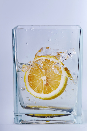Half a lemon is in a glass vessel with water. Drops, trickles, air bubbles.