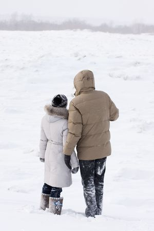 loving couple on the shore of frozen river 스톡 사진