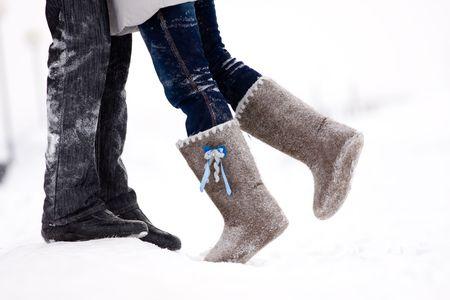 필드의 중간에 눈 덮인 겨울에 서있는 커플을 포용하는 다리