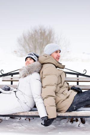 ropa de invierno: joven pareja sentada en un banco con su espalda entre s� Foto de archivo