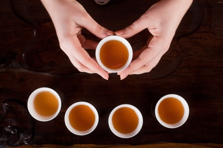 hands holding a cup of tea but there are a number of other cups of tea