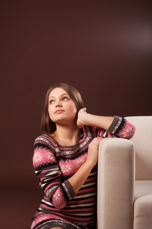 the girl looks up sitting at the couch Stock Photo - 8716111