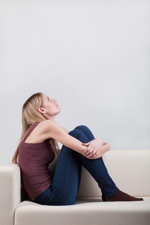 mujeres sentadas: chica sentado en el sof�, abrazando sus piernas de armas