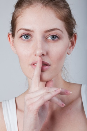 quieter: she holds a finger to his mouth calls to be quieter Stock Photo