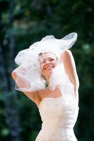 joyful bride squinting from the sun