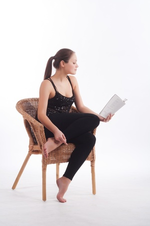 girl reading a book on a wicker chair photo