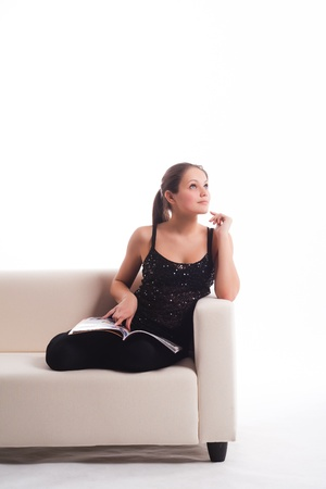 adult magazine: girl on the couch with a magazine sitting dreaming