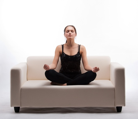 woman meditating in lotus position on the couch Stock Photo - 8855765