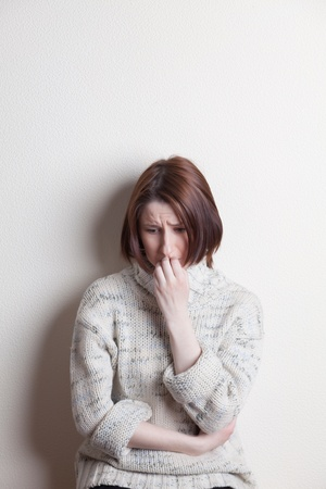 distraught woman standing against a wall