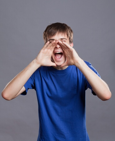 young man shouting attaching hands to his mouth Stock Photo