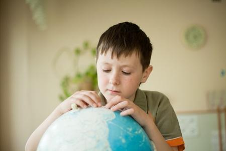 schoolkid search: ni�o estudiando diligentemente globo Foto de archivo
