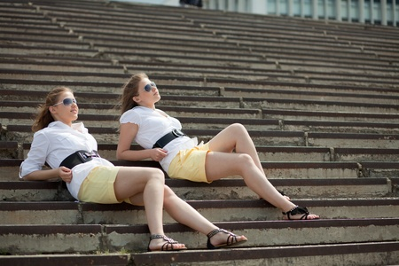 girls are twins on the steps and look into the distance 스톡 사진