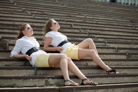 girls are twins on the steps and look into the distance Stock Photo